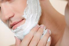 Stock Photo of Close-up of man applying shaving mean
