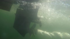 An underwater shot of a motor and propellar on a boat on a lake Stock Footage