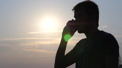 Man silhouette talking on cell phone against the sun in evening time Stock Footage
