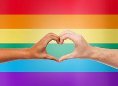 human hands showing heart shape over rainbow - stock photo