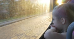 Little Blonde Girl in Pink Shirt is Sitting at the Window in the Bus, Tram, Arkistovideo