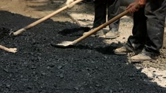 Workers Stack Asphalt on the Road Stock Footage