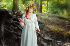 Romantic girl standing in the woods. Stock Photos