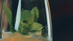 Mint leaves are falling in a glass of lemonade Stock Footage