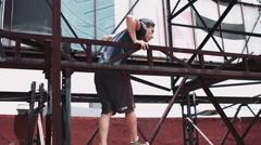 Man climbing on scaffolding - stock footage