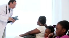 Pediatrician doctor talking to the mother of two black children Stock Footage