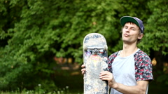 Guy Having Fun with a Skateboard in His Hand Stock Footage