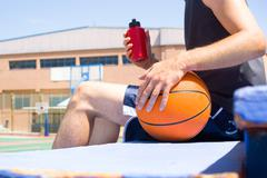 Young man with a basketball behind a fence Stock Photos