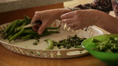 Houswife prepare pods ( broad bean ) for dinner at home Stock Footage