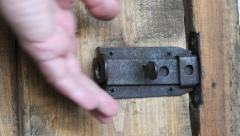 Hand closes and open old wooden door with an iron latch - stock footage
