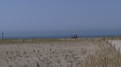 Stock Video Footage of Elderly cyclists across dune crest in a new created coastal area