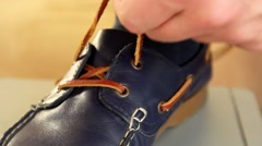 YOUNG MAN TO TIE THE LACES IN SHOES Stock Footage