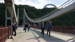 People on Suspension Bridge Family Day Green Forest on a River Bank Walkers Are - stock footage