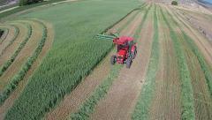 Aerial farmer in tractor cutting wheat grain field HD - stock footage