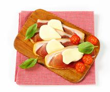 Sliced prosciutto crudo and mozzarella with fresh basil and tomatoes Stock Photos
