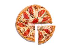 Top view of tasty Italian pizza with ham and tomatoes with a slice removed - stock photo