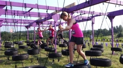 woman in pink tank top walking across tires in an obstacle course - stock footage