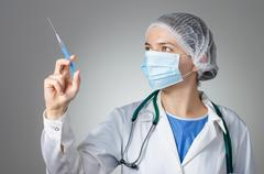 Female doctor with syringe - stock photo
