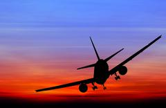 Silhouetted commercial airplane flying at sunset - stock photo