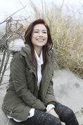 Portrait of woman in parka on winter beach Stock Photos