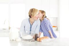 Girl (4-5) whispering into mom's ear - stock photo