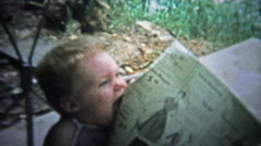 TENNESSEE, USA - 1954: Baby eating the sunday newspaper at the kitchen table. Stock Footage