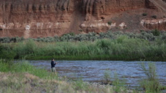 MAN FISHING ALONE ON SCENIC RIVER WITH LARGE RED CLIFFS IN BACKGROUND Stock Footage