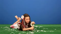 Girl 6 Years Old Lying on the Grass and Separates From the Chamomile Petals Stock Footage
