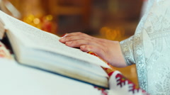 Hand the priest lying on open Bible Stock Footage