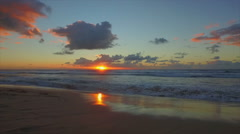 SLOW MOTION: Waves rolling up the sandy beach at sunset Stock Footage