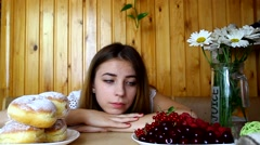 A young girl sitting at a table, looking for food, the choice of diet Stock Footage