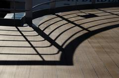 shadow of railing at the bottom of ship - stock photo