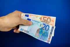 Stock Photo of hand holding out two banknotes
