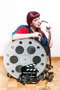 Young woman smile behind big movie cinema reel biting filmstrip Stock Photos