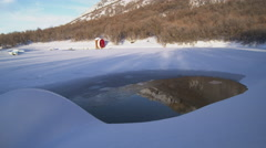 Time lapse of red water wheel on edge of snow-covered frozen lake and hill Stock Footage