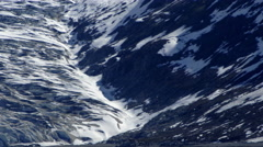 Traveling view of the side of a glacier and the side of a snow covered mountain Stock Footage