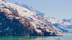 View from the side of a traveling cruise ship of snow covered rocky mountains Stock Footage