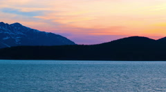 Traveling time-lapse of a sunset behind mountains and water near Haines, Alaska. Stock Footage