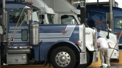 Truckers cleaning their rigs at a gas station rest stop - stock footage