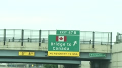Driving by Bridge to Canada sign Stock Footage