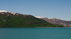 Time lapse view of green, rocky, snow capped mountains surrounded by glassy blue Stock Footage