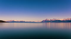 Time lapse view of snow capped mountains along the glassy water in Alaska. Stock Footage