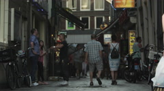 Static shot of people walking and talking on a small street in Amsterdam Stock Footage