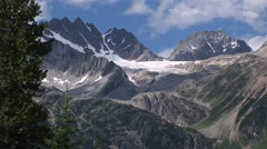 Mountain glacier framed by trees against a brilliant blue sky. - stock footage