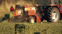 Shot of a farmer operating a hay baler as he goes around the field Stock Footage