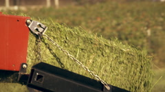 Medium shot of a hay baler dropping a bale of hay on the ground Stock Footage