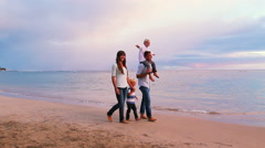 Happy Young Caucasian Family Walking on Sandy Beach Stock Footage