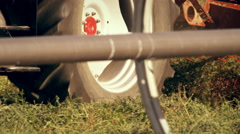 Medium shot of a hay baler as seen from behind a wheel irrigation system Stock Footage