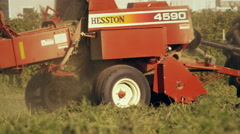 Medium shot of a square hay baler Stock Footage