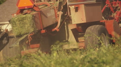 Shot of a square hay baler going around the farm as it turns piles of hay into Stock Footage